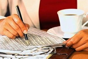 Businesswoman Writing in a Newspaper